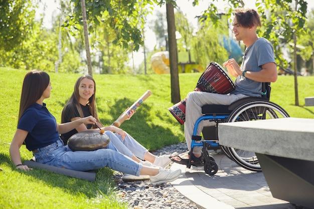 Glücklicher behinderter mann auf einem rollstuhl, der zeit mit freunden verbringt, die live-instrumentalmusik im freien spielen.