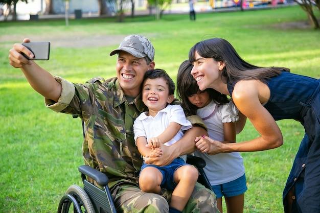 Glücklicher behinderter militärmann, der selfie mit seiner frau und zwei kindern im park nimmt. veteran des krieges oder der freizeit mit familienkonzept