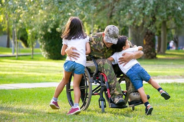 Glücklicher behinderter militärmann im rollstuhl, der nach hause zurückkehrt und kinder umarmt. kriegsveteran oder familientreffen konzept
