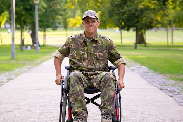 Glücklicher behinderter militärmann im rollstuhl, der tarnuniform trägt und sich auf fußweg im stadtpark bewegt. vorderansicht. kriegsveteran oder behindertenkonzept