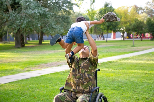 Glücklicher behinderter militärvater im rollstuhl, der nach hause zurückkehrt und sohn umarmt, jungen in den armen hält und ihn anhebt. kriegsveteran oder familientreffen konzept