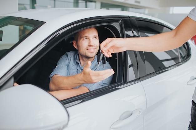 Glücklicher besitzer eines weißen autos, das darin sitzt und manager betrachtet, der ihm schlüssel gibt. junger mann streckt seine hand aus. der andere ist am lenkrad.