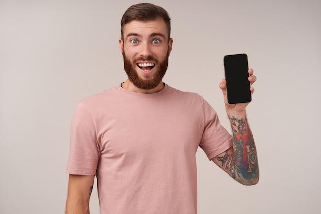 Glücklicher blauäugiger hübscher bärtiger mann mit tätowierungen, die beige t-shirt tragen, während auf weiß posieren, freudig lächeln und hand mit smartphone darin heben