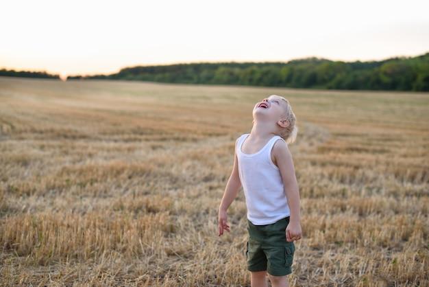 Glücklicher blonder junge steht mit dem kopf oben auf einem gemähten weizenfeld. sonnenuntergangszeit