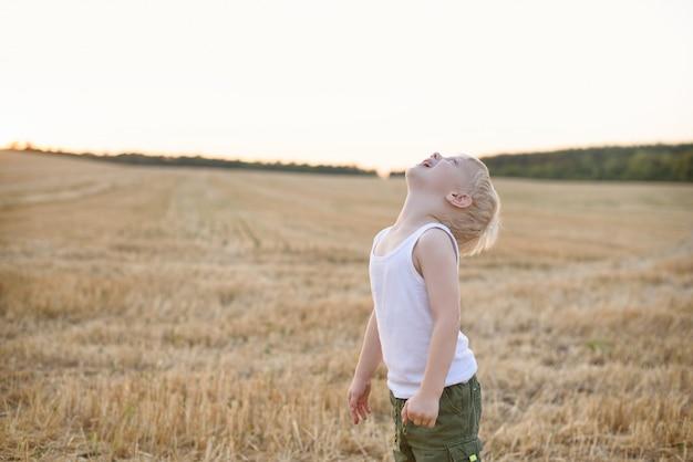 Glücklicher blonder junge steht mit seinem kopf oben auf einem gemähten weizenfeld. sonnenuntergang