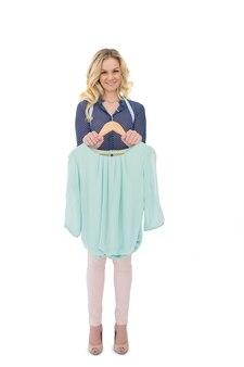 Glücklicher blonder modedesigner, der bluse hält