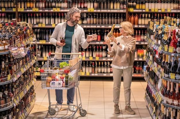 Glücklicher blonder reifer weiblicher kunde, der ihren ehemann flasche wein zeigt, während beide zwischen regalen mit alkoholischen getränken stehen