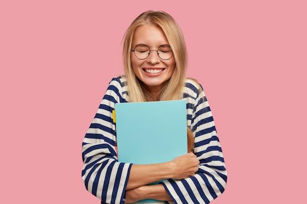 Glücklicher blonder student, der gegen die rosa wand aufwirft