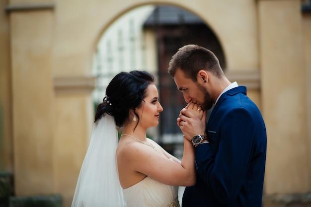 Glücklicher bräutigam küsst die hand seiner geliebten frau