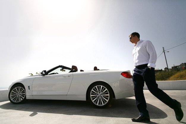 Glücklicher bräutigam nahe dem auto