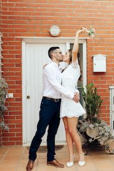 Glücklicher bräutigam und braut, die küssen umarmen und ihren arm mit ihrem hochzeitsstrauß nach der zeremonie heben. hochzeitskonzept.