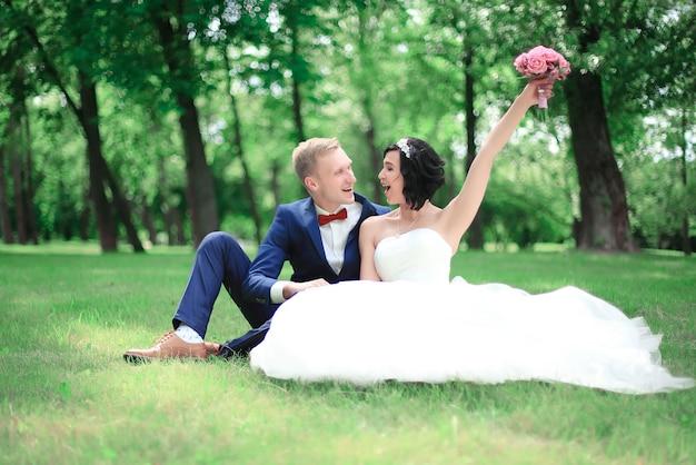 Glücklicher bräutigam und braut sitzen im rasen