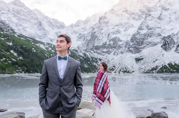 Glücklicher bräutigam und braut stehen auseinander nahe dem zugefrorenen see, umgeben von schneebedeckten bergen