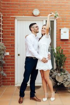 Glücklicher bräutigam und braut umarmen und heben ihren arm mit ihrem hochzeitsstrauß nach der zeremonie. hochzeitskonzept.