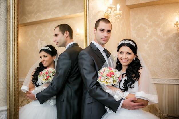 Glücklicher bräutigam und die braut stehen nahe einem spiegel und werden in ihm reflektiert