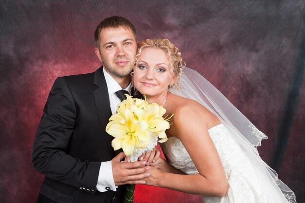 Glücklicher bräutigam und die reizend braut mit einem blumenstrauß von den gelben lilien im studio