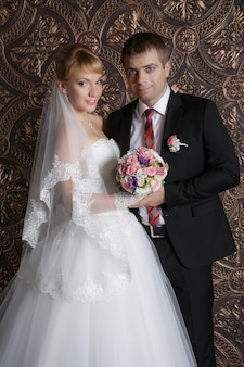 Glücklicher bräutigam und die reizend braut mit einem blumenstrauß von den rosen im studio auf einem braun