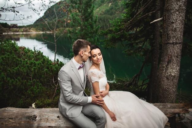Glücklicher bräutigam und seine reizend neue frau, die beim sitzen auf dem ufer von waldsee morskie oko sich hält