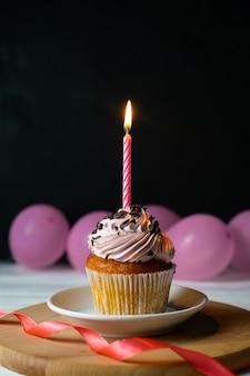 Glücklicher brithday kleiner kuchen mit einer kerze auf schwarzem mit rosa ballonen
