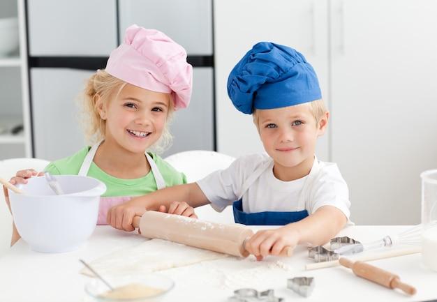 Glücklicher bruder und schwester, die einen teig steht in der küche vorbereitet