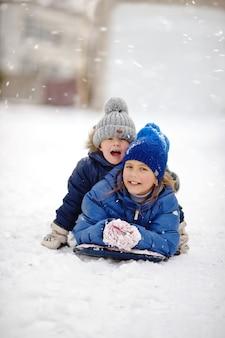 Glücklicher bruder und schwester spielen auf dem schnee