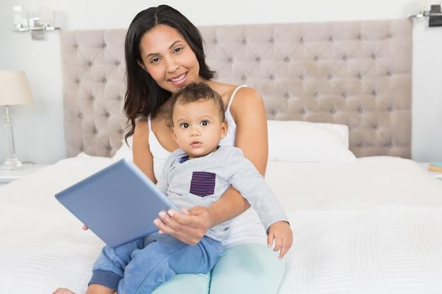Glücklicher brunette, der ihr baby hält und tablette im schlafzimmer verwendet