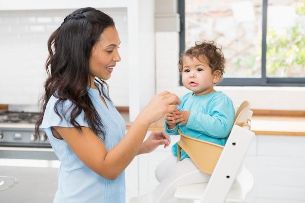 Glücklicher brunette, der ihr baby in der küche einzieht