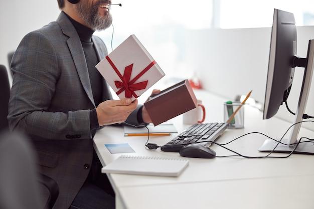Glücklicher büroangestellter hält ein geschenk und lächelt