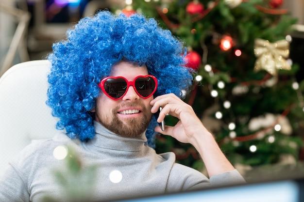 Glücklicher büroangestellter in der sonnenbrille und in der blauen lockigen perücke, die durch smartphone am arbeitsplatz am weihnachtstag sprechen