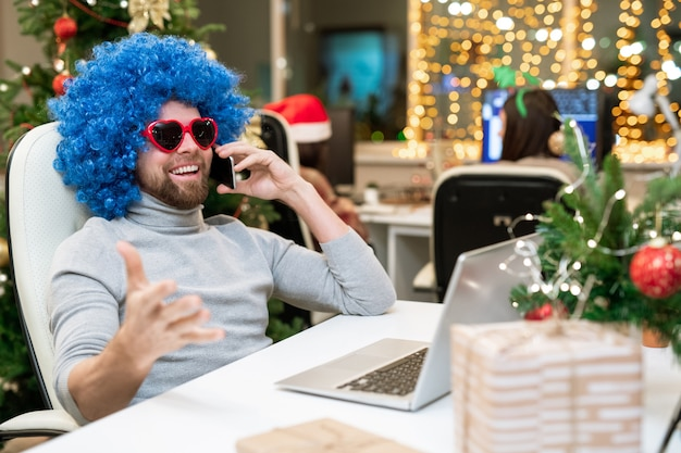 Glücklicher büroangestellter in der sonnenbrille und in der blauen lockigen perücke, die geschäftspartnern am telefon vor laptop gratulieren