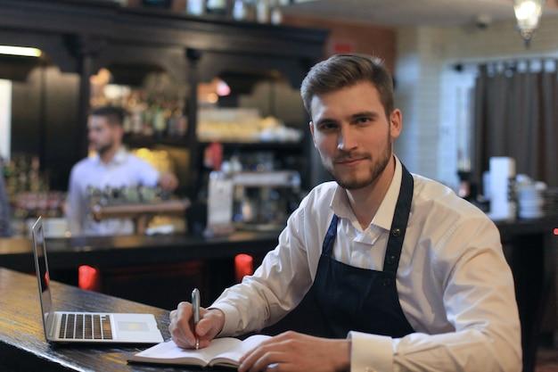 Glücklicher café-manager, der rezepte mit laptop zählt.