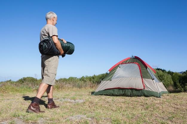 Glücklicher camper, der in richtung zu seinem zelt geht, der schlafsack hält
