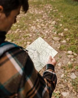 Glücklicher campingmann im wald, der auf der karte schaut