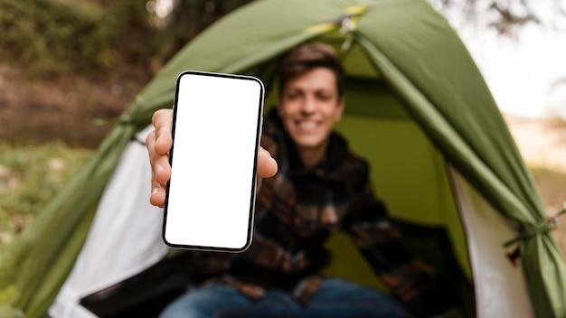 Glücklicher campingmann im waldkopierraum-mobiltelefon