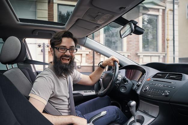 Glücklicher charismatischer mann, der ein auto fährt