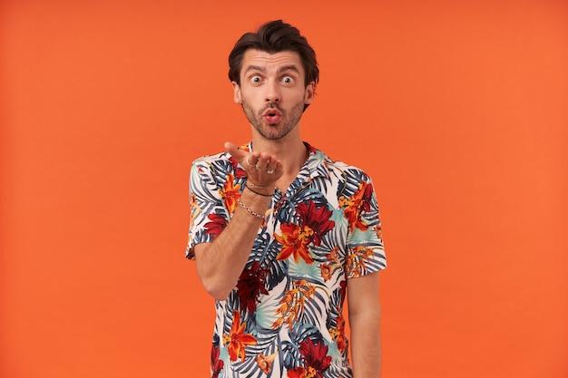 Glücklicher charmanter junger mann mit borsten im bunten hemd, das steht und einen kuss zur kamera sendet