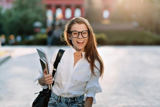 Glücklicher charmanter student im weißen hemd, das sich auf das lernen vorbereitet