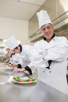 Glücklicher chef mit anderen, die salate vorbereiten