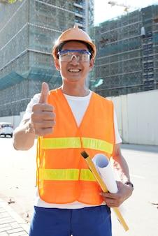 Glücklicher chefingenieur, der auf der baustelle mit ebener und gerollter blaupause steht und daumen hoch zeigt