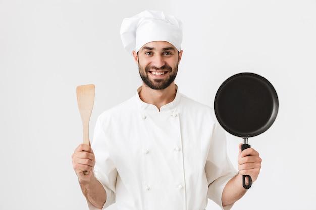 Glücklicher chefmann in kochuniform, der holzküchenspatel und bratpfanne isoliert über weißer wand hält