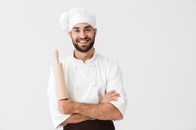 Glücklicher chefmann in kochuniform, der lächelt, während er küchenholz-nudelholz isoliert über weißer wand hält?