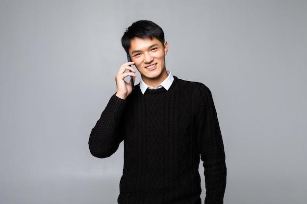 Glücklicher chinesischer mann, der ein smartphone verwendet gegen weiße wand isoliert.