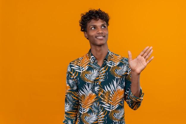 Glücklicher denkender junger gutaussehender mann im hemd, das hand winkt