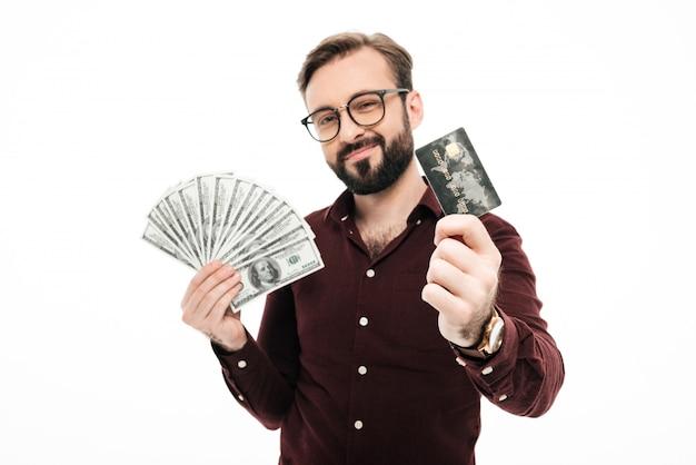 Glücklicher denkender junger mann, der geld und kreditkarte hält.