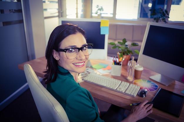 Glücklicher designer, der an der kamera lächelt
