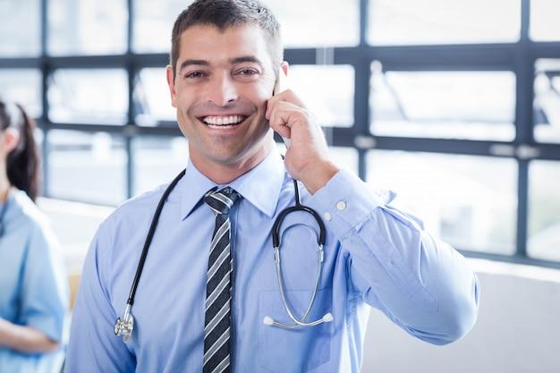 Glücklicher doktor am telefon im krankenhaus