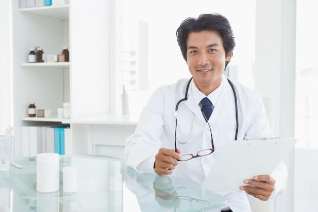 Glücklicher doktor, der an seinem schreibtisch sitzt