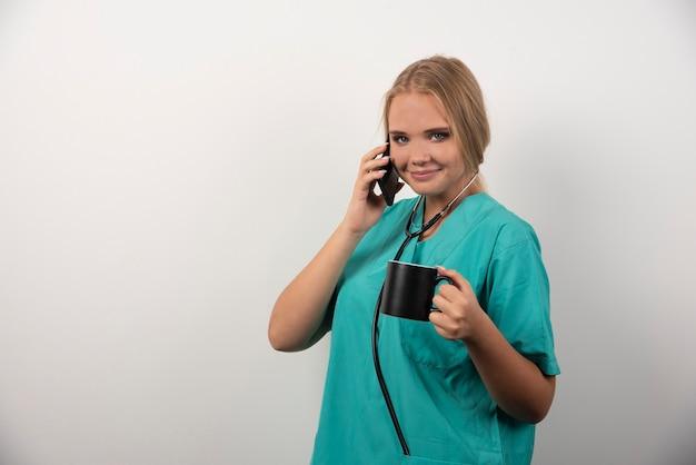 Glücklicher doktor, der tee beim gespräch mit telefon hält.