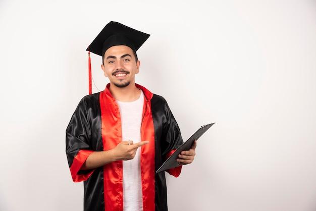 Glücklicher doktorand, der auf sein diplom auf weiß zeigt.