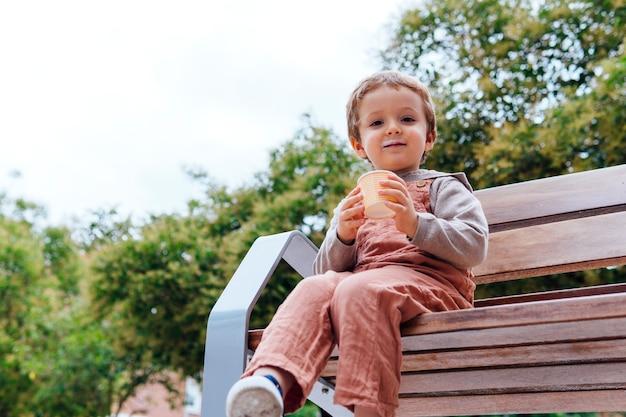 Glücklicher dreijähriger junge auf der straße, der auf einer bank einen becher eis hält